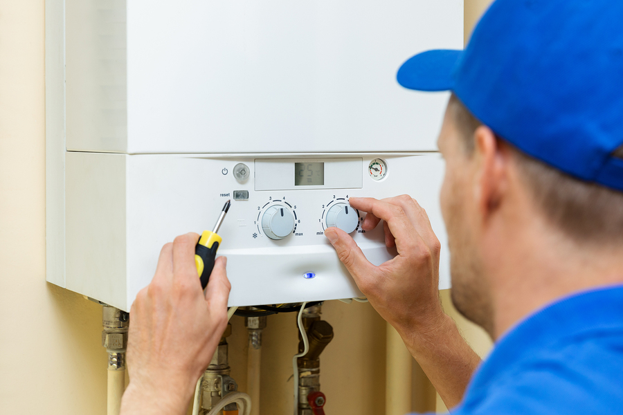 Worker setting up system for hot water cylinders