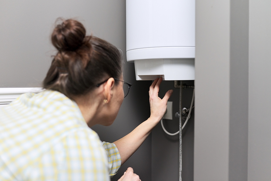 Woman regulating the temperature of a hot water cylinder